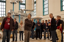 Uwe Stephan (3rd from right) and Michael Hensel (4th from right) show the students the high voltage test hall of HIGHVOLT